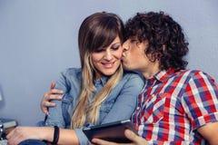 Homme embrassant à la jeune femme et tenant le comprimé Image stock