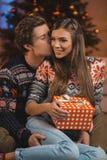 homme embrassant l'amie heureuse avec le cadeau de Noël Photo libre de droits