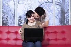 Homme embrassant son épouse tandis que salaire en ligne Photographie stock libre de droits