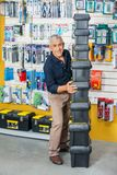 Homme empilant des boîtes à outils dans le magasin de matériel Photographie stock libre de droits