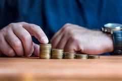 Homme empilant l'argent dans le diagramme photographie stock