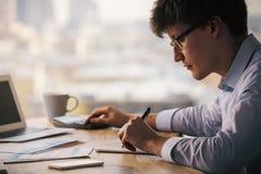 Homme employant la calculatrice et l'inscription Images libres de droits