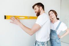 Homme employant la grande règle tandis que sa femme presque se tenant Photo libre de droits