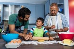 Homme employant la table tout en se tenant prêt le père et le fils préparant la nourriture Image stock