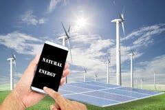 Homme employant le contrôle futé mobile de téléphone avec les panneaux solaires, turb de vent image stock
