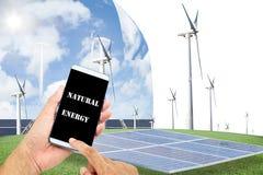 Homme employant le contrôle futé mobile de téléphone avec les panneaux solaires, turb de vent photographie stock
