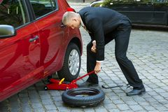 Homme employant le cric hydraulique rouge de plancher pour la réparation de voiture Image libre de droits