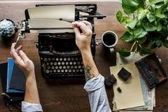 Homme employant le rétro auteur Changing Paper de travail de machine de machine à écrire Photographie stock libre de droits