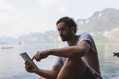 Homme employant le sien téléphone par un lac images stock