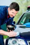 Homme employant une serviette absorbante pour sécher la surface d'une voiture image libre de droits