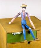 Homme en bois peint à la main avec le dollar dans la boîte Images stock