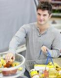 Homme en bonne santé avec les fruits de achat d'achat-panier Images stock