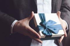 Homme en cadeau de offre de costume avec le ruban bleu Photographie stock libre de droits