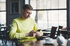 Homme en café avec un téléphone Images stock