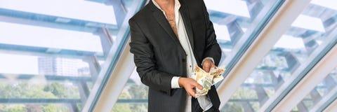 Homme en désordre dans le costume avec l'argent Photographie stock libre de droits