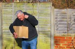 Homme en douleur portant la boîte lourde Tension d'épaule Photos stock