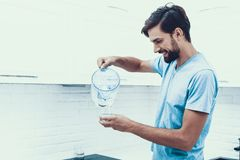 Homme en eau potable de chemise dans la cuisine à la maison photo stock