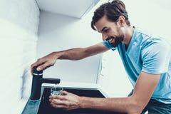 Homme en eau potable de chemise dans la cuisine à la maison photos stock