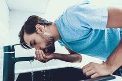 Homme en eau potable de chemise dans la cuisine à la maison images libres de droits