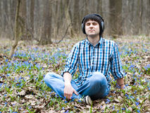 Homme en fleur de écoute de musique d'écouteurs au printemps Photo stock