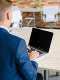 Homme en gros plan dactylographiant sur un ordinateur portable numérique sur un fond clair Concept utile de l'électronique photos stock