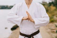 Homme en gros plan dans le kimono dans une pose de salutation sur un fond naturel Homme montrant le signe de coupure Le sport pra photographie stock