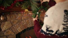Homme en guirlande accrochante kniited de Noël de chandail au-dessus de la cheminée authentique en pierre décorée de la guirlande banque de vidéos