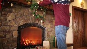 Homme en guirlande accrochante kniited de Noël de chandail au-dessus de la cheminée authentique en pierre décorée de la guirlande clips vidéos