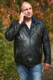 Homme en parc d'automne avec le téléphone Photo stock