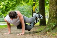 Homme en parc de ville faisant le sport d'entraîneur de suspension Images stock