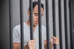 Homme en prison derrière des barres photo stock