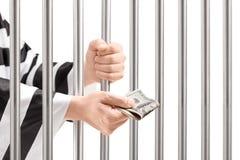 Homme en prison tenant des barres de prison et donnant le paiement illicite Photographie stock