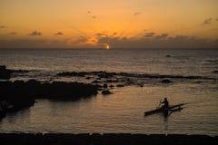 Homme en silhouette de bateau en île de Pâques pendant le coucher du soleil Chili image stock