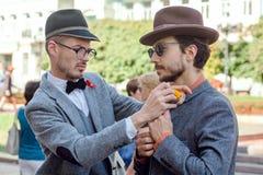 Homme en verres ajustant le costume de vintage de l'ami dans la foule du festival en Europe Photographie stock libre de droits