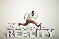Homme en verres de réalité virtuelle fonctionnant entre les mots au-dessus du blanc Photographie stock