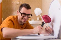 Homme en verres nettoyant la cuvette des toilettes Photographie stock
