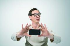 Homme en verres photographiés par le smartphone Photographie stock