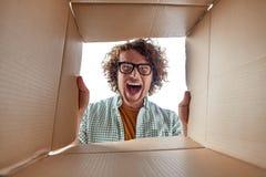 Homme en verres regardant à l'intérieur de la boîte photo stock