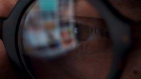 Homme en verres regardant sur le moniteur et l'Internet surfant L'écran de moniteur est reflété dans les verres banque de vidéos