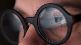 Homme en verres regardant sur le moniteur et l'Internet surfant L'écran de moniteur est reflété dans les verres clips vidéos