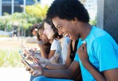 Homme encourageant d'afro-américain avec le téléphone portable et les amis Photographie stock libre de droits