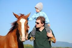 Homme, enfant et cheval images stock