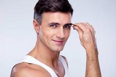 Homme enlevant des poils de sourcil avec s'épiler image libre de droits