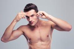 Homme enlevant des poils de sourcil avec s'épiler photo stock