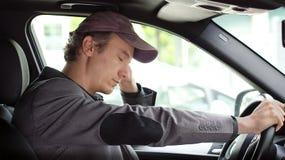 Homme ennuyé à la roue de son sommeil de voiture Image libre de droits