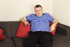Homme ennuyé avec à télécommande Image stock