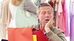 Homme ennuyé avec des paniers se reposant devant son amie banque de vidéos