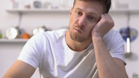 Homme ennuyé mangeant lentement de la céréale insipide avec du lait, rêves au sujet de petit déjeuner savoureux banque de vidéos