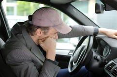 Homme ennuyé sur sa voiture attendant dans un embouteillage Photographie stock libre de droits