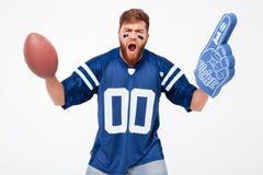 Homme enthousiaste avec la boule de rugby et doigt de fan encourageant  Images stock
